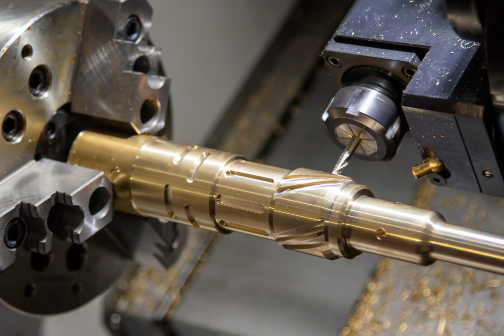 A CNC machine making grooves in a brass part.