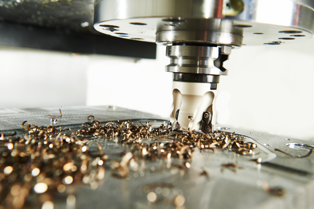 A close up view of a CNC mill with metal shavings.